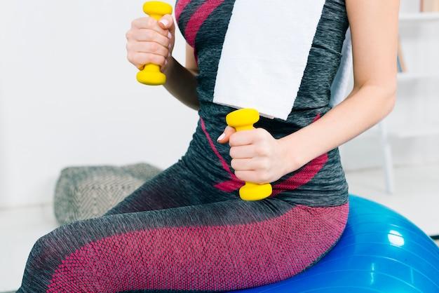 W połowie sekcja ćwiczy z żółtymi dumbbells młoda kobieta Darmowe Zdjęcia
