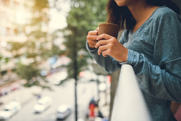 W Połowie Sekcja Pije Herbacianą Pozycję Przy Balkonem Kobieta Darmowe Zdjęcia