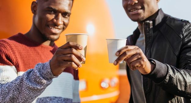 W Połowie Strzał Czarnych Mężczyzn Pijących Kawę Przy Food Trucku Darmowe Zdjęcia