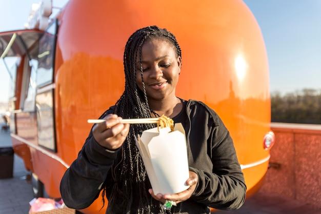 W Połowie Strzał Kobieta Jedzenie Chińskie Jedzenie W Pobliżu Ciężarówki Z Jedzeniem Premium Zdjęcia