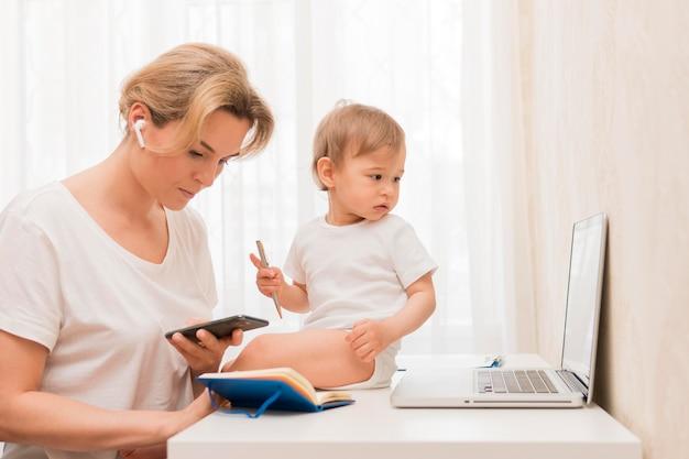 W Połowie Strzał Matka Patrzeje Telefon I Dziecka Na Biurku Darmowe Zdjęcia