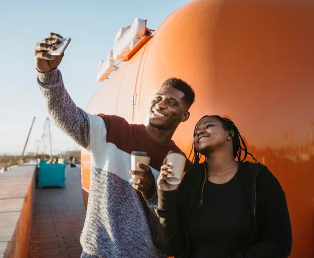 W Połowie Strzał Mężczyzna I Kobieta Robią Selfie Przy Food Trucku Darmowe Zdjęcia