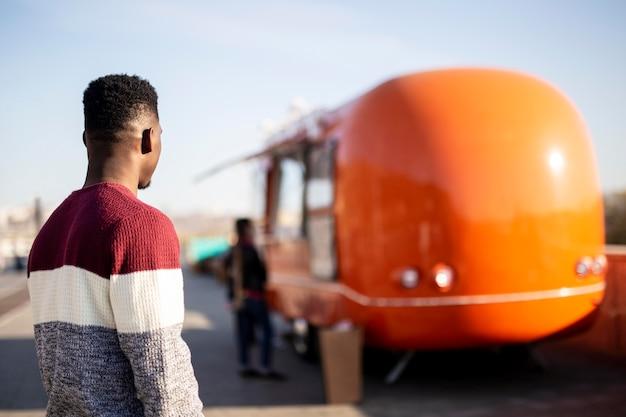 W Połowie Strzał Mężczyzna Idący W Kierunku Food Trucka Darmowe Zdjęcia