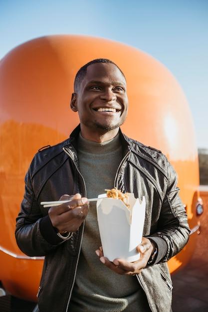 W Połowie Strzał Mężczyzna Je Chińskie Jedzenie W Pobliżu Ciężarówki Z Jedzeniem Premium Zdjęcia