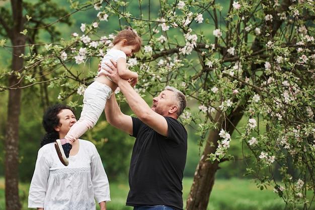 W Rękach Dziadka. Wesoła Para Spędza Miły Weekend Na świeżym Powietrzu Z Wnuczką. Dobra Wiosenna Pogoda Darmowe Zdjęcia