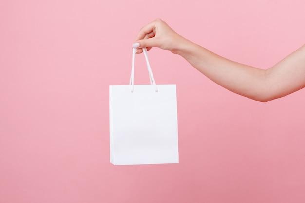 W Ręku Biała Torebka Pod Logo Na Różowej Przestrzeni Premium Zdjęcia