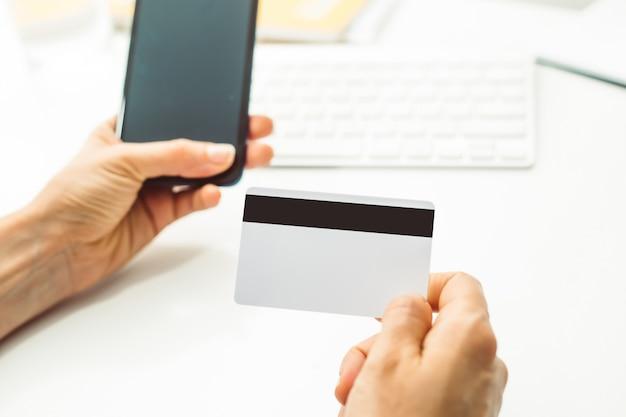 W ręku jest pusta biała karta kredytowa i telefon komórkowy do płatności internetowych. Premium Zdjęcia
