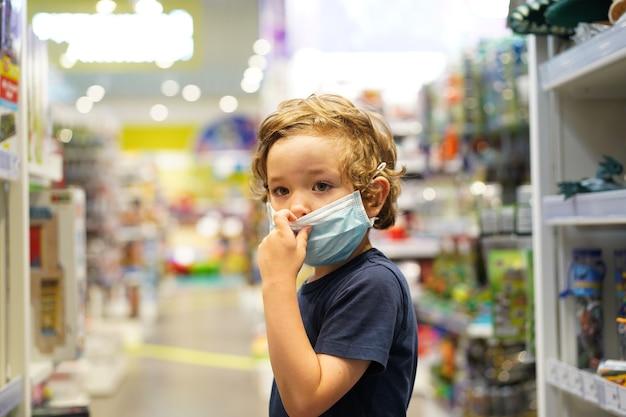 W Sklepie Dziecko Nosi Maskę Ochronną. Bezpieczeństwo, Ochrona Zdrowia Podczas Kwarantanny Covid-19. Premium Zdjęcia