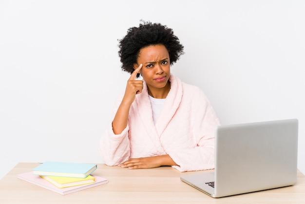 W średnim Wieku Amerykanin Afrykańskiego Pochodzenia Kobieta Pracuje W Domu Wskazujący świątynię Z Palcem, Myśleć, Skupiający Się Na Zadaniu. Premium Zdjęcia