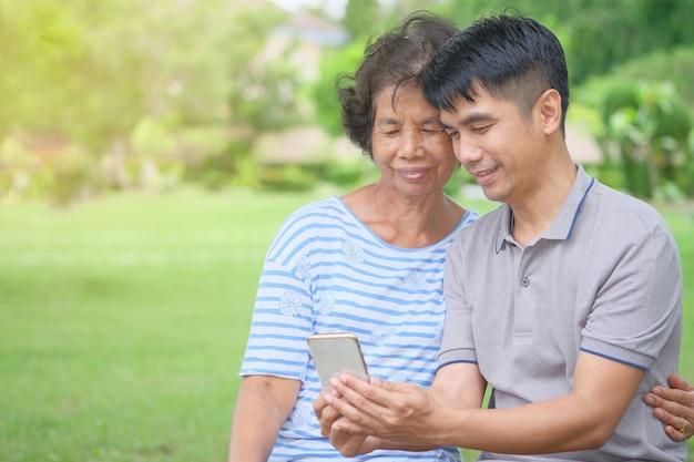 W średnim wieku azjatycka matka i syn patrzenie na smartfona z uśmiechem i bycie szczęśliwym w parku to imponujące ciepło Premium Zdjęcia