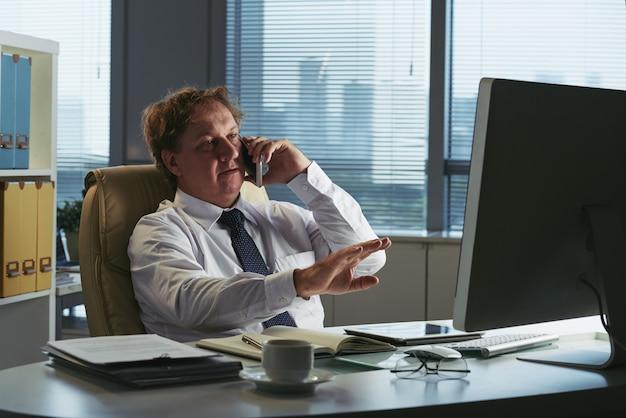W średnim wieku biznesmen opowiada na telefonie i gestykuluje Darmowe Zdjęcia