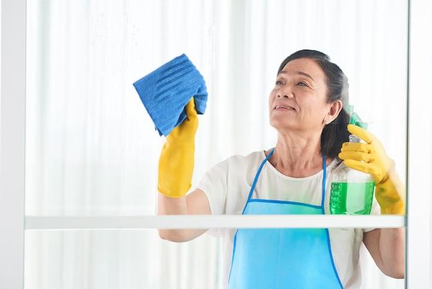 W średnim wieku gospodyni wyciera okno środkiem do czyszczenia w sprayu Darmowe Zdjęcia