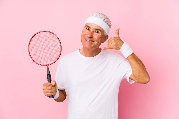 W średnim Wieku Mężczyzna Bawić Się Badminton Odizolowywającego Pokazywać Gesta Rozmowy Telefonicznej Palca. Premium Zdjęcia