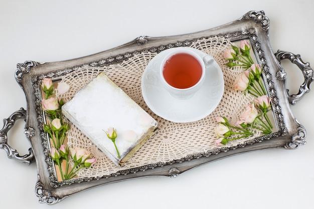 W Starej Srebrnej Koronkowej Serwetce, Pączkach Róży, Filiżance Herbaty I Książce Premium Zdjęcia
