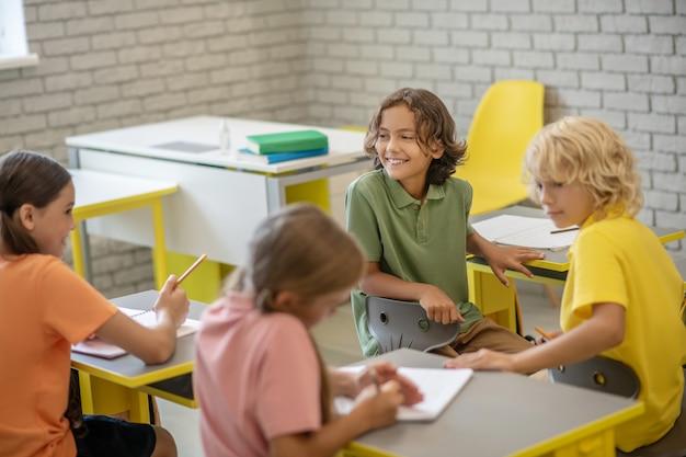 W Szkole. Dzieci Siedzą Przy ławkach W Klasie I Wyglądają Na Zadowolone Premium Zdjęcia
