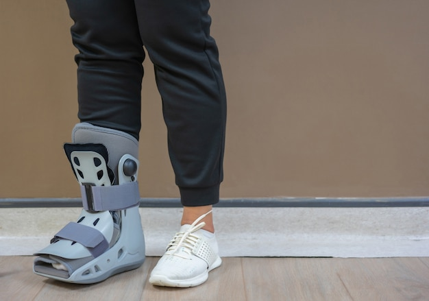 W szpitalu pacjenci cierpieli na złamanie kostki, co wymagało założenia buta ortopedycznego. Premium Zdjęcia