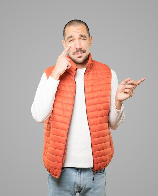 Wahający Młody Człowiek Gestem Ostrożności Z Ręką Wskazującą Na Oko Premium Zdjęcia