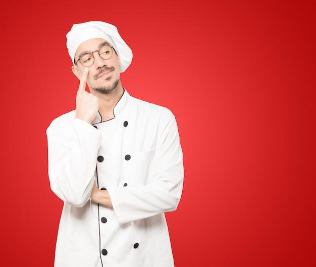 Wahający Młody Szef Kuchni Gestem Ostrożności Z Ręką Wskazującą Na Oko Premium Zdjęcia