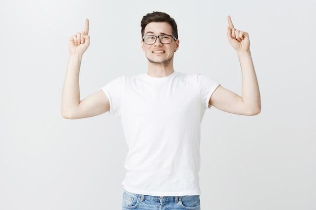 Wahający Się Niezręczny Facet W Okularach Wskazujący Palcami W Górę I Wyglądający Na Zmartwionego Darmowe Zdjęcia