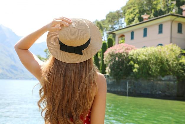 Wakacje Nad Jeziorem Como. Widok Z Tyłu Podróży Turystycznych Dziewczyna Relaksujący Widok Na Krajobraz Jeziora Como Z Miasta Bellagio We Włoszech. Premium Zdjęcia