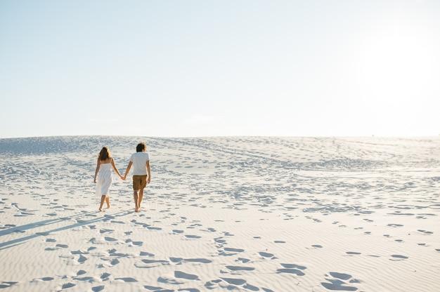 Wakacje Para Razem Spaceru Na Plaży W Miłości, Trzymając Się Wokół Siebie. Szczęśliwa Międzyrasowa Młoda Para. Premium Zdjęcia