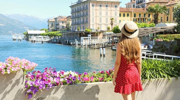 Wakacje W Bellagio. Widok Młodej Dziewczyny Z Tyłu Widok Na Miasto Bellagio Nad Jeziorem Como We Włoszech. Premium Zdjęcia