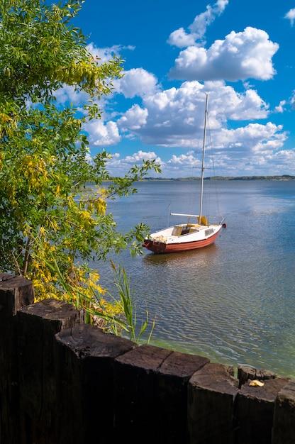 Wakacje Wakacje Podróży Pojęcie: żaglówka Jacht Przy Rzeką Obok Brzeg W Lecie Na Chmurnym Niebie Premium Zdjęcia