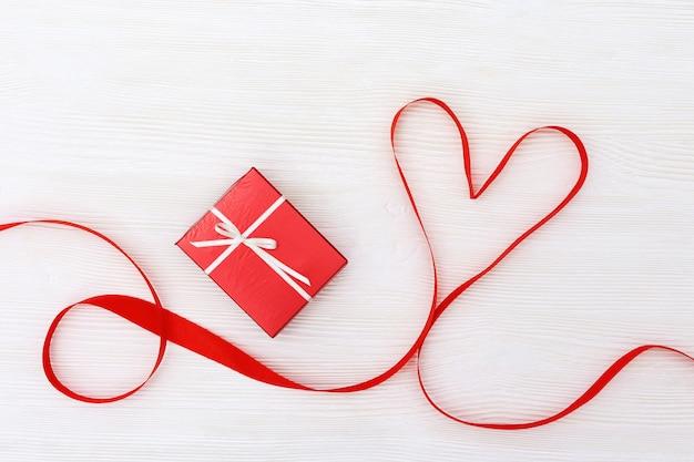 Wakacyjny tło z prezentem i sercem na białym drewnie. Premium Zdjęcia