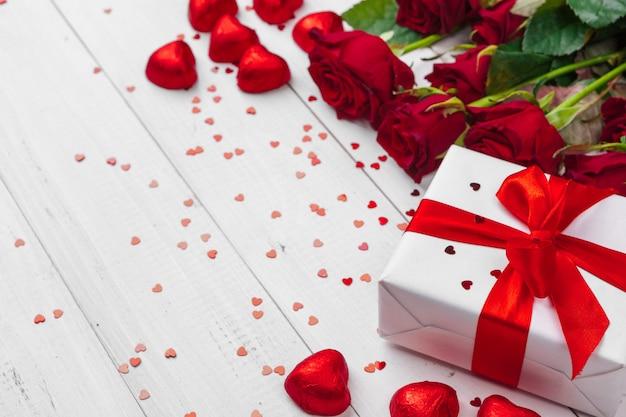 Walentynki. czerwone róże i pudełko na drewnianym stole Premium Zdjęcia