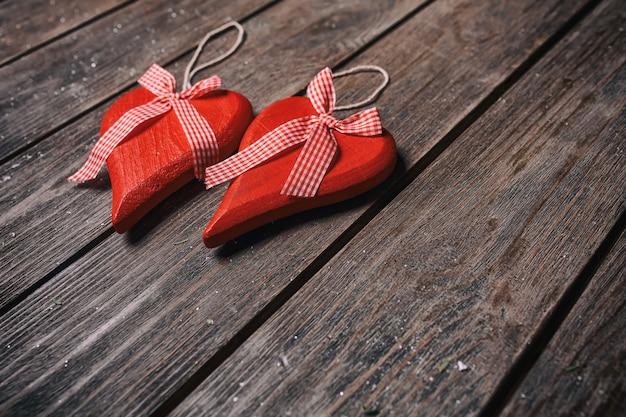 Walentynki-dzień tło. para czerwoni serca zw kratkę faborkiem na drewnianym tle. Premium Zdjęcia