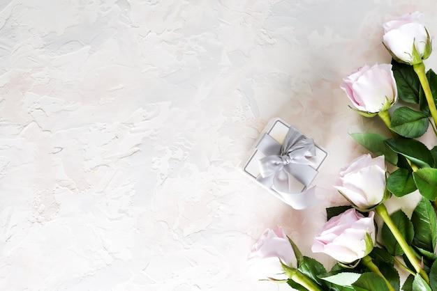 Walentynki kartkę z życzeniami. różowe róże i prezenta pudełko na światło kamieniu, odgórny widok z copyspace Premium Zdjęcia