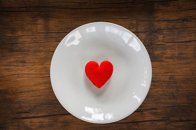 Walentynki kolacja romantyczna miłość jedzenie i miłość gotowania czerwone serce na białym talerzu romantyczny stół ustawienie ozdobione czerwonym sercem drewniane Premium Zdjęcia