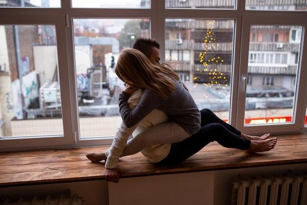 Walentynki. Koncepcja Miłości, Szczęścia, Ludzi I Zabawy. Piękny Pary Przytulenie Podczas Gdy Siedzący Na Nadokiennym Parapecie W Domu. Premium Zdjęcia