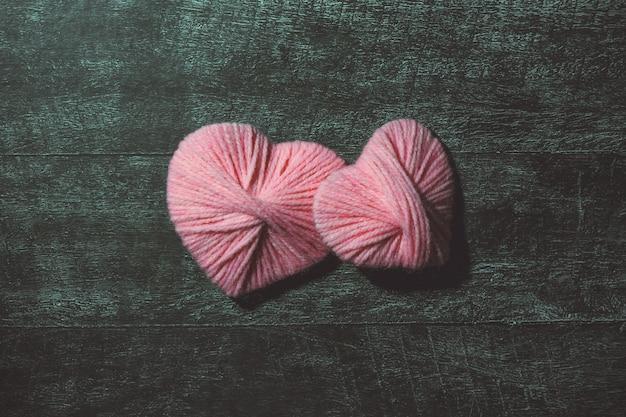 Walentynki. ręcznie wykonane ozdobne nici różowe serca na ciemnym drewnianym stole. koncepcja miłości. kartka z życzeniami. copyspace Premium Zdjęcia