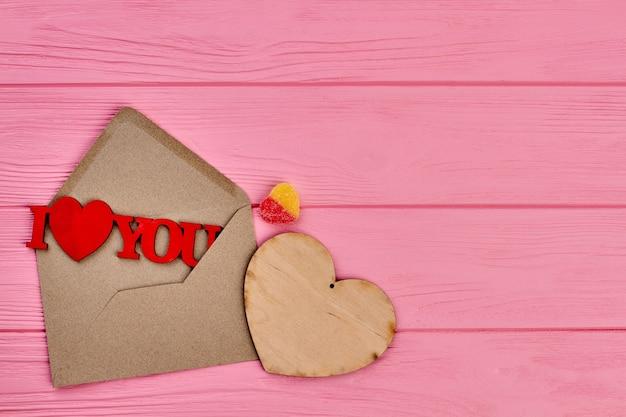 Walentynki Różowe Tło Drewniane. Koperta Z Drewnianą Figurą Kocham Cię, Serce Ze Sklejki I Cukierki W Kształcie Serca, Kopia Przestrzeń. Premium Zdjęcia
