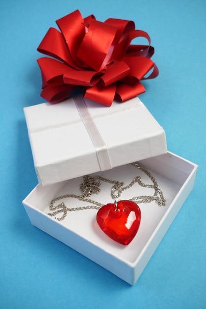 Walentynkowa Kompozycja Z Czerwonym Sercem Wisiorek W Obecnym Pudełku Na Niebieskim Tle Premium Zdjęcia