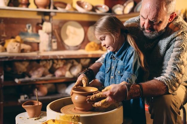 Warsztaty garncarskie. dziadek uczy ceramiki wnuczki. modelowanie gliny Premium Zdjęcia