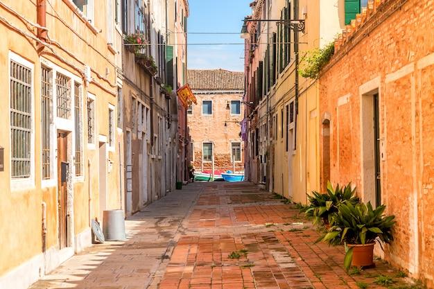 Wąska ulica murano z kolorowymi domami i roślinami w wczesnym poranku w wenecja, włochy. Premium Zdjęcia