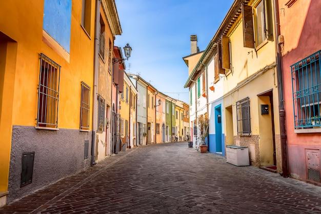 Wąska ulica wioska rybacy san guiliano z kolorowymi domami i bicyklami w wczesnym poranku w rimini, włochy. Premium Zdjęcia
