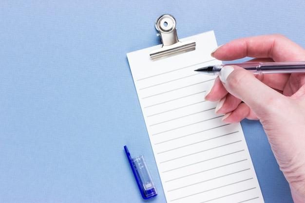 Ważna Biznesowa Lista Kontrolna, Planowanie Przypomnień O Zakupach Lub Lista Zadań Priorytetowych Projektu Na Niebieskim Tle Z Miejsca Kopiowania. Pióro W Rękach Kobiet Premium Zdjęcia