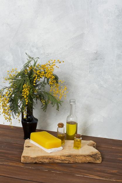 Wazon żółty Kwiat Mimozy Z Ziołowe Mydło I Butelka Olejku Na Drewnianej Desce Nad Stołem Przeciwko Szarej ścianie Darmowe Zdjęcia