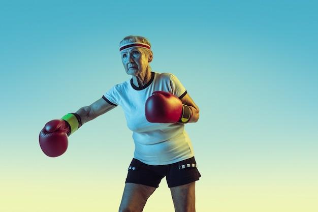 Wciąż Kopie. Starszy Kobieta W Boksie Sportowym Na Gradiencie Darmowe Zdjęcia