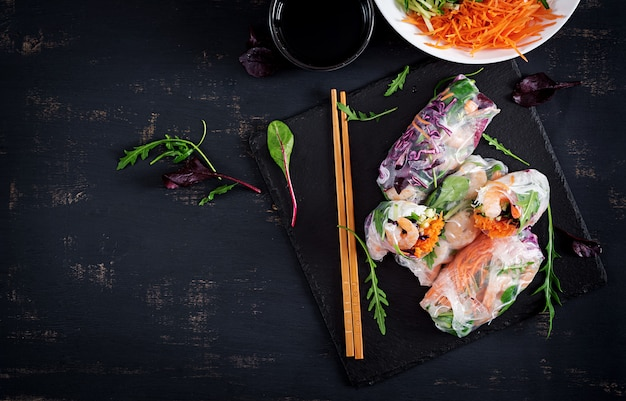Wegetariańskie wietnamskie sajgonki z pikantnymi krewetkami, krewetkami, marchewką, ogórkiem, czerwoną kapustą i makaronem ryżowym. Premium Zdjęcia