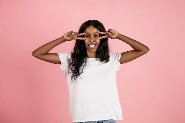 Wesoła Afroamerykańska Młoda Kobieta Na Białym Tle Na Koralowej Przestrzeni, Emocjonalne I Wyraziste Darmowe Zdjęcia
