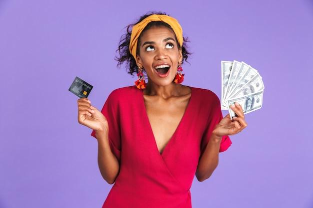 Wesoła Afrykańska Kobieta W Sukni, Trzymając Pieniądze I Kartę Kredytową, Patrząc Na Fioletową ścianę Premium Zdjęcia