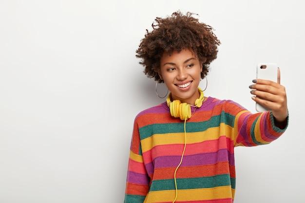 Wesoła Ciemnoskóra Kobieta O Ciemnych Kręconych Włosach, Robi Selfie Za Pomocą Smartfona, Ubrana W Kolorowy Sweter, Uśmiecha Się Delikatnie, Stoi Na Białym Tle, Z Boku Puste Miejsce Darmowe Zdjęcia