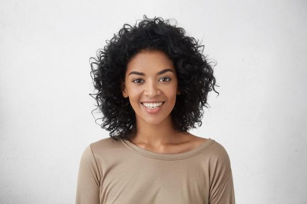 Wesoła Ciemnoskóra Kobieta, Szeroko Uśmiechnięta, Radująca Się Ze Zwycięstwa W Rywalizacji Młodych Pisarzy, Stojąca Odizolowana Od Szarej ściany. Koncepcja Ludzie, Sukces, Młodość I Szczęście Darmowe Zdjęcia