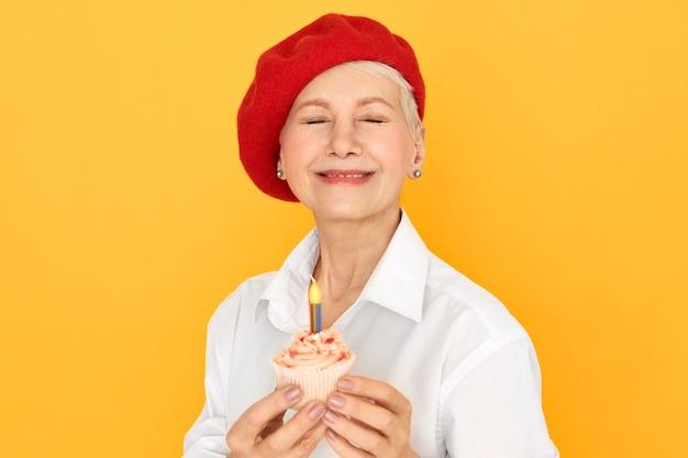 Wesoła Dojrzała Kobieta Ubrana W Elegancką Czerwoną Czapeczkę Zamykająca Oczy, Składająca życzenia Na Urodziny Darmowe Zdjęcia