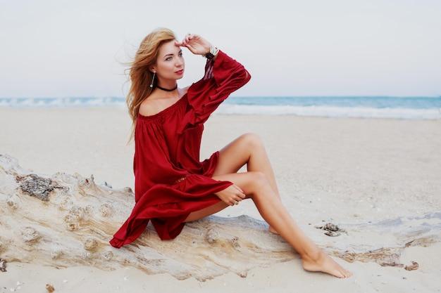 Wesoła Dziewczyna Ruda Pozowanie Na Plaży. Siedząc Na Białym Piasku. Wietrzne Włosy. Modny Ubiór. Portret Styl życia. Nastrój W Podróży. Wybrzeże Oceanu. Darmowe Zdjęcia