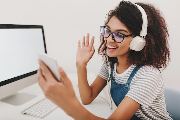 Wesoła Dziewczyna W Stylowej Koszuli I Słuchawkach Komunikuje Się Z Przyjacielem Za Pomocą Linku Wideo Darmowe Zdjęcia